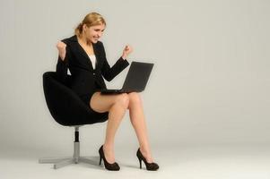 junge attraktive Frau mit Laptop, der in einem Stuhl sitzt foto
