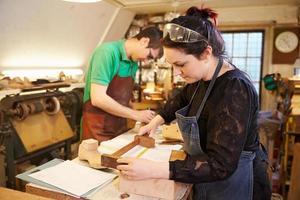 Zwei junge Schuhmacher, die Schuhvorbereitungen in einer Werkstatt vorbereiten foto