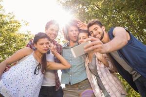 glückliche Freunde im Park, die selfie nehmen foto