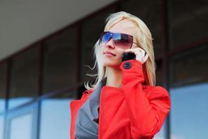 junge Frau, die am Telefon gegen Bürofenster anruft foto