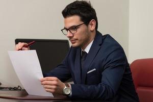 junger Geschäftsmann im Büro, der Papier betrachtet foto