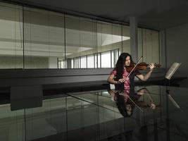 Frau, die Geige im Geschäftsbüro spielt foto