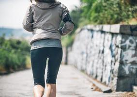 Nahaufnahme auf Frau, die im Stadtpark joggt. Rückansicht foto