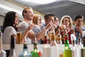 glückliche Freunde, die Cocktails in Schnapsgläser halten foto