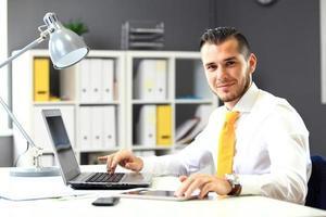 schöner Geschäftsmann, der mit Laptop im Büro arbeitet foto