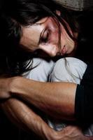 Person, die ihre Knie mit verletztem Gesicht umarmt foto