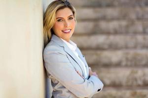Geschäftsfrau an Bürowand gelehnt foto
