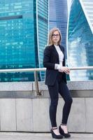 Geschäftsfrau, die mit Kaffee auf dem Hintergrund der Wolkenkratzer steht foto