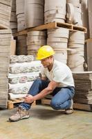 Arbeiter mit verstauchtem Knöchel auf dem Boden foto