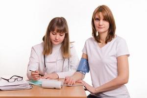 Der Arzt schreibt die Tonometerwerte in die Patientenkarte foto