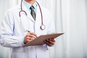 Arzt, der Daten aufzeichnet foto