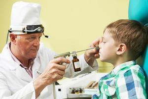 kleiner Junge an der Ohrnase des Arztes foto