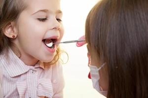Kind mit Zahnarzt mit Werkzeug, um in den Mund zu schauen foto