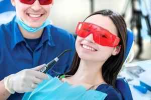 gesunde Zähne bei einem Patienten. lächelnder Zahnarzt behebt foto