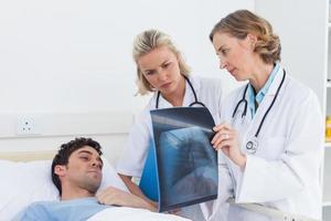 Ärzte, die einem Patienten Röntgenaufnahmen zeigen foto