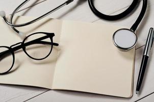 Notizbuch mit leeren Seiten mit Stethoskop öffnen