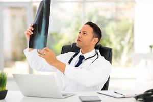 Arzt mittleren Alters, der die Röntgenaufnahme des Patienten betrachtet foto