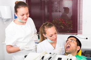 Zahnarzt untersucht Patienten in der Klinik foto