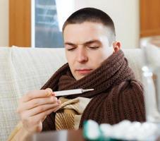 Mann misst Temperatur mit Thermometer
