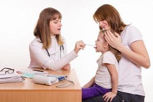 Kinderarzt, der in das Kehlkind schaut, das auf Schoß der Mutter sitzt