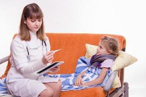 Kinderarzt überprüfen Temperatur auf Thermometer kleines Mädchen foto