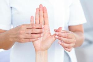 Physiotherapeutin untersucht die Hand ihrer Patienten foto