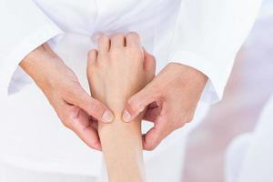 Arzt untersucht das Handgelenk ihrer Patienten foto