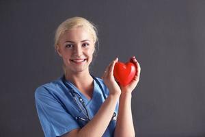 Arzt mit Stethoskop, das Herz hält, lokalisiert auf grauem Hintergrund foto