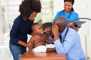 männlicher afrikanischer Arzt, der kleinen Jungen untersucht foto