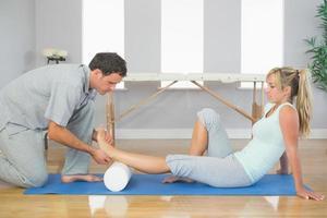 Physiotherapeut untersucht den Fuß des Patienten, während er auf dem Boden sitzt foto