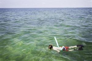 junger jugendlich Junge, der weg von Schlüssel West Florida schnorchelt foto