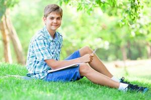 jugendlich Junge mit Büchern und Notizbuch im Park. foto