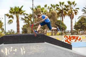 Teen Boy fährt mit seinem Roller im Skatepark foto