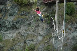 eine Frau Bungee springt von einer Brücke foto