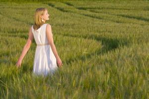 Teenager-Mädchen, das durch Gerstenfeld geht foto