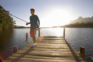 Teenager, der Angelrute und Fisch auf dem Steg des Sees trägt foto