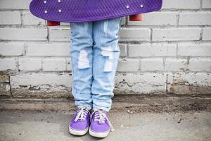 Teenagerfüße in Blue Jeans mit Skateboard