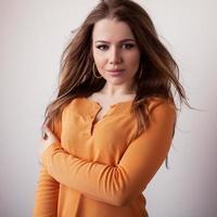 junges Schönheitsmodellmädchen im lässigen orangefarbenen Pullover. foto