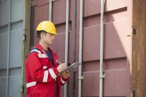 männlicher Arbeiter, der Frachtcontainer inspiziert foto