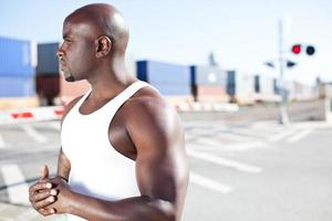 junger schwarzer Mann durch Bahngleise foto