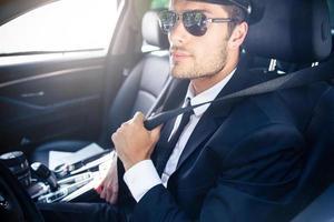 männlicher Chauffeur, der in einem Auto sitzt foto