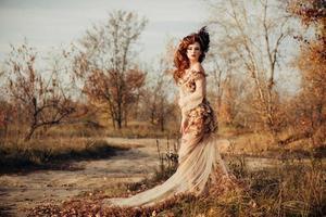 Schönheit Herbstfrau im Kleid mit Blättern