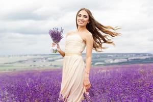hübsches lächelndes Mädchen trägt Kleid am lila Lavendelfeld foto