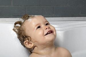glücklicher kleiner Junge im Bad foto
