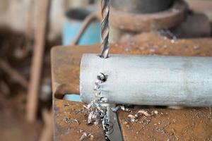 Metallbohren mit einem großen Bohrer in einer Werkstatt foto