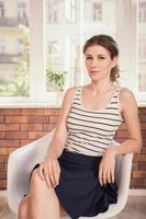 positive Geschäftsfrau, die auf dem Stuhl sitzt foto