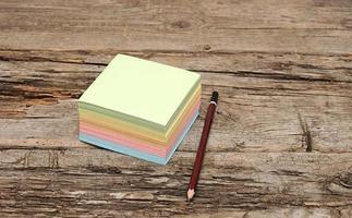 Papiernotiz und Bleistift auf hölzernem Hintergrund foto