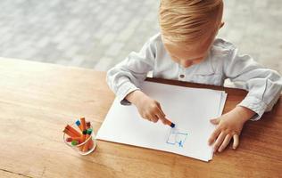 kleiner Junge, der auf einem Tisch im Freien zeichnet foto