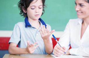 Hand des Kindes, das Mathe mit Lehrer lernt