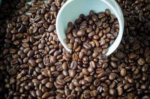 weiße Tasse mit Kaffeebohnen foto